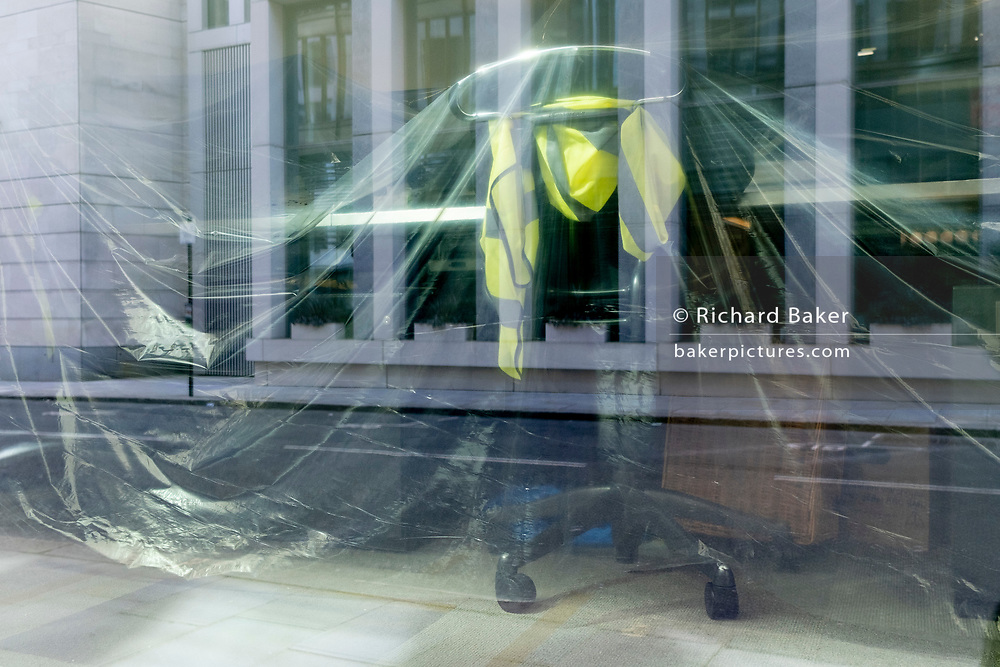 Office fixtures including seats and the hi-vis tabard of a company safety officer and furniture are wrapped by plastic dust covers over the Easter weekend and during the third lockdown of the Coronavirus pandemic, in the City of London - the capital's financial district, on 4th April 2021, in London, England.