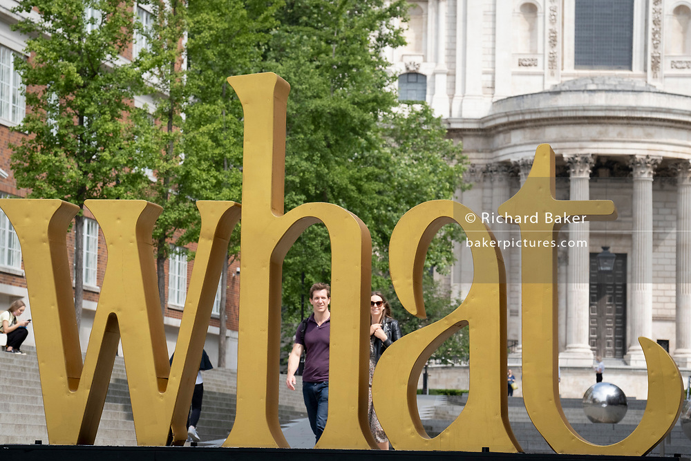 With St Paul's Cathedral in the distance, the philosophical pronoun word 'What' is in the foreground on Peter's Hill in the City of London, the capital's financial district, on 24th June 2021, in London, England. This word is one of many others along a  route around several major attractions including the Millennium Bridge, St Paul's Cathedral, Museum of London and the Barbican Centre and will help orientate the spaces around Culture Mile. Each installation acts as a way finding tool and sculptural attractor where people can be informed about Culture Mile and the area. The distance between each installation allows the pedestrian to be guided between the last and the next word long the route. CREDIT RICHARD BAKER.