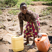 A young woman washes her jerrycans in a stream before filling up with water at a new reservoir build by IMA and Tearfund in her community near Butembo, Congo.