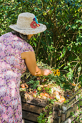 Senior woman in a garden with compost heap, Altoetting, Bavaria, Germany