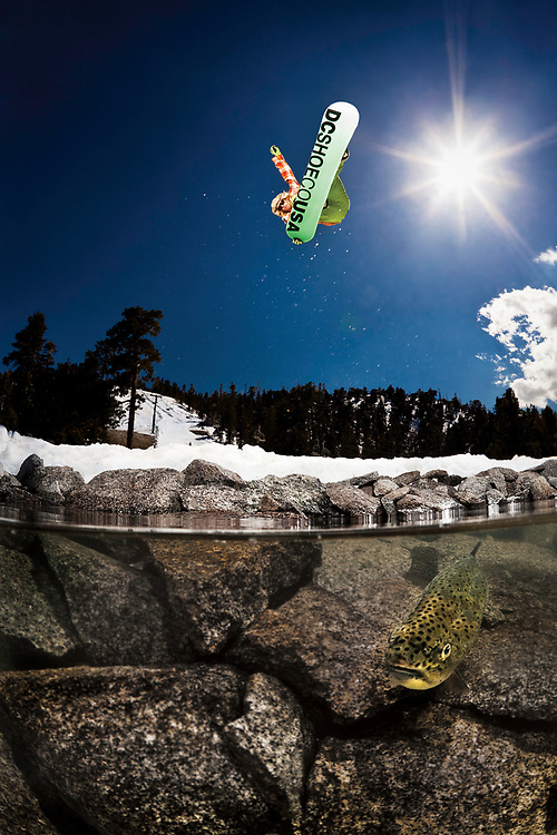 Ever since I first bought my water housing to photograph surfing, I had been looking for ways to use it for snowboarding. To create the shot I wanted I needed two key components, legit snowboard action and clear water.<br /> <br /> I started to get jobs working with Red Bull, and they would come up with these crazy ideas and then build what they wanted. This is when I realized that I could just build the components that I needed and shoot it in a semi controlled environment. <br /> <br /> I had my housing equipped with a 20 foot custom sync cord so that I could fire the strobes from under the water using a Pocket Wizard remote. When it came to lighting the scene, I knew that I would need at least one strobe to light the fish and rocks. For this, I set up a Profoto Acute 600 at full power and directed it down, right in front of me. The idea of having waterproof lights in the water was consided but I didn't think it would make much of a difference when considering the extra cost involved. This shot was going to be backlit so I was going to need all the fill light I could get. For this, I set up a Profoto 7b, able to fire 2 strobes. I used one with a narrow beam reflector on the left side as fill light and the other head on the right side just to help eliminate motion blur.<br /> <br /> Finally it was time to have the fish swim into the frame. I thought this was going to be easier than it was. Eventually Clayton Shoemaker jumped into the water with me to help wrangle them into position. Fish food didn't work. I would yell up to Lauri every time a fish was in the frame and he would drop in. After about 25 attempts we had the shot.