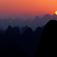 Sun rises over landscape of myriad silhouetted karst towers, Yangshuo, Guilin, China