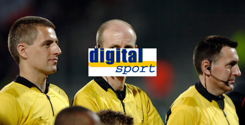 Photo: Daniel Hambury.<br />Lyon v PSV Eindhoven. UEFA Champions League. 03/08/2006.<br />English referee MIke Riley and his two assistants David Babski (L) and Peter Kirk wear microphone headsets as they take charge of the match.