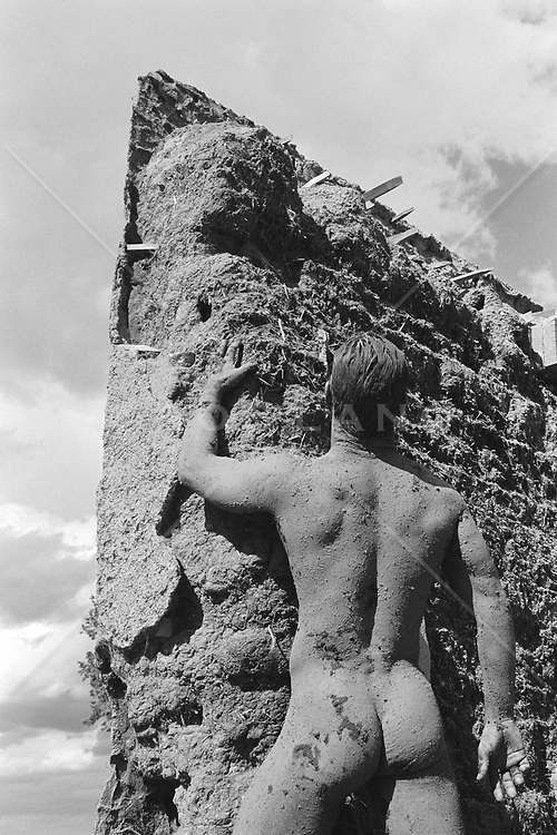rear view of nude man covered in mud against an adobe wall