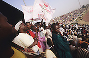 Christians, of Sabon Gari football team supporters at a match in Kano..The implementation of Islamic Sharia Law across the twelve northern states of Nigeria, centres upon Kano, the largest Muslim Husa city, under the feudal, political and economic rule of the Emir of Kano. Islamic Sharia Law is enforced by official state apparatus including military and police, Islamic schools and education, plus various volunteer Militia groups supported financially and politically by the Emir and other business and political bodies. Fanatical Islamic Sharia religious traditions  are enforced by the Hispah Sharia police. Deliquancy is controlled by the Vigilantes volunteer Militia. Activities such as Animist Pagan Voodoo ceremonies, playing music, drinking and gambling, normally outlawed under Sharia law exist as many parts of the rural and urban areas are controlled by local Mafia, ghetto gangs and rural hunters. The fight for control is never ending between the Emir, government forces, the Mafia and independent militias and gangs. This is fueled by rising petrol costs, and that 70% of the population live below the poverty line. Kano, Kano State, Northern Nigeria, Africa