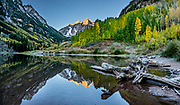 The Maroon Bells and yellow aspen leaves reflect in Maroon Lake at sunrise. The Maroon Bells are two adjacent peaks of the Elk Mountains: Maroon Peak 14,163 feet on left, seen behind North Maroon Peak 14,019 feet, in Maroon Bells-Snowmass Wilderness of White River National Forest. The mountains are on the border between Pitkin County and Gunnison County, about 12 miles southwest of Aspen, in Colorado, USA. This image was stitched from multiple overlapping photos.