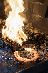 Red hot horseshoe in burning stack, Bavaria, Germany
