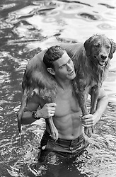 man carrying a Golden Retriever Dog over his shoulders in a lake