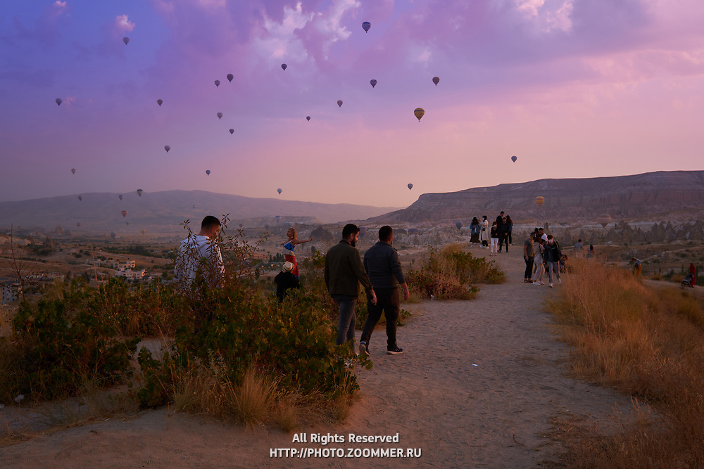 Tourists walk to the Goreme viewpoint to see hot air balloons, Cappadocia