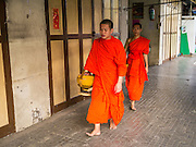 19 OCTOBER 2012 - BANGKOK, THAILAND:   Buddhist monks walk through the old section of Bangkok, Thailand, near Wat Po and Tha Tien Pier, on their morning alms rounds.    PHOTO BY JACK KURTZ