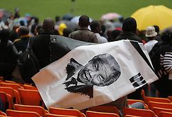 Mandela Memorial Service.<br /> 60812719<br />  Supporters hold a poster of Nelson Mandela before the memorial service for the former South African president at the FNB Stadium in Soweto near Johannesburg, South Africa, Tuesday, 10th December 2013. Picture by  imago / i-Images<br /> <br /> UK ONLY
