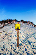 Cliff and sand dunes along the shoreline shows signs of continued erosion. Warning sign. Cape Cod, Massachusetts, USA