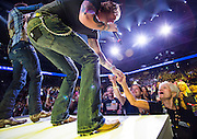 Corporate photography of Tyler Hubbard reaches for the hand of an associate as he performs with Brain Kelley, both with Florida Georgia Line, during the 2014 annual Wal-Mart Shareholder's Meeting in Fayetteville, Ark., for Wal-Mart Stores Inc.