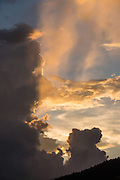 Sunset rays shine through orange-yellow clouds and blue sky over the Dolomites, Italy, Europe.