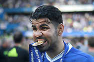 Diego Costa of Chelsea takes a bite out of his winners medal. Premier league match, Chelsea v Sunderland at Stamford Bridge in London on Sunday 21st May 2017.<br /> pic by Steffan Bowen,  Andrew Orchard sports photography.
