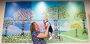 25 July 2017: Born Into A City of Culture - Hull and East Yorkshire Women and Childrens Hospital.<br /> During 2017, every baby born in Hull, East Yorkshire,  has been invited to have their footprint taken for a commissioned piece of artwork called 'Born Into A City of Culture'. Each month a new panel has been added to the foyer of Hull and East Yorkshire Women and Childrens Hospital. The artwork will be completed in January 2018.<br /> Over 2300 babies footprints have been taken so far. To mark the half-way point, a mother and baby born in each month from January to June, were invited back to look at the artwork. <br /> The tree trunks are hand-prints of midwives.<br /> The artwork has been produced by Hull design company Jenko.<br /> <br /> Pictured is Tina Dixon and 13 week old Freddie.<br /> <br /> <br /> Picture: Sean Spencer/Hull News & Pictures Ltd<br /> 01482 210267/07976 433960<br /> www.hullnews.co.uk         sean@hullnews.co.uk