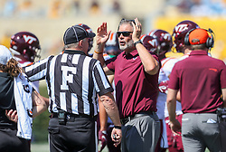 Sep 18, 2021; Morgantown, West Virginia, USA; Virginia Tech Hokies head coach Justin Fuente talks to a referee during the first quarter against the West Virginia Mountaineers at Mountaineer Field at Milan Puskar Stadium. Mandatory Credit: Ben Queen-USA TODAY Sports
