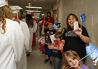 Graduating seniors are greeted by Pleasant Street School students and faculty including Carmelle Ryan who had many of the seniors in her Kindergarten class.  (Karen Bobotas/for the Laconia Daily Sun)