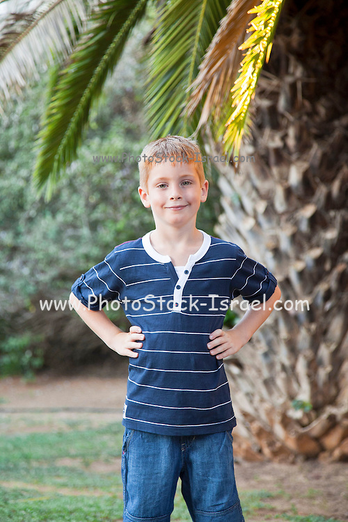 Portrait of a young happy and confident red haired boy of seven outdoors