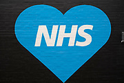 NHS heart shaped street art in Birmingham city centre, which is virtually deserted under Coronavirus lockdown on a wet rainy afternoon on 28th April 2020 in Birmingham, England, United Kingdom. Britains second city has been in a state of redevelopment for some years now, but with many outdated architectural remnants still remaining, on a grey day, the urban landscape appears as if frozen in time. Coronavirus or Covid-19 is a new respiratory illness that has not previously been seen in humans. While much or Europe has been placed into lockdown, the UK government has put in place more stringent rules as part of their long term strategy, and in particular social distancing.