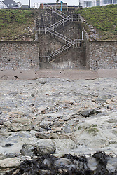 © Licensed to London News Pictures. 02/03/2018. FALMOUTH CORNWALL, UK. Beach washed away, steps left high and dry now leading to rocks instead of the sandy beach. Storm Emma caused damage to the beaches and businesses of Falmouth at the morning high spring tide today. The strong wind and the spring tide caused a beach to be washed away at Gylly beach. At Swanpool beach the beach was washed onto the road causing it to be blocked .  Photo credit: MARK HEMSWORTH/LNP