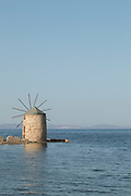 Calm blue sea with famous historical stone windmill at Tampakika, Chios, Greece