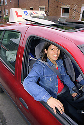 Young woman with cerebral palsy sitting in specially adapted car for the disabled,