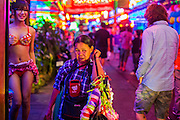 "12 JANUARY 2013 - BANGKOK, THAILAND:  A woman who sells garters to workers in the red light district of Soi Cowboy walks down the street between ""Ladyboy"" entertainers and tourists. In Thai, the ladyboys are called kathoey. Many work in the entertainment and night life sectors of the Thai economy.  Prostitution in Thailand is illegal, although in practice it is tolerated and partly regulated. Prostitution is practiced openly throughout the country. The number of prostitutes is difficult to determine, estimates vary widely. Since the Vietnam War, Thailand has gained international notoriety among travelers from many countries as a sex tourism destination. One estimate published in 2003 placed the trade at US$ 4.3 billion per year or about three percent of the Thai economy. It has been suggested that at least 10% of tourist dollars may be spent on the sex trade. According to a 2001 report by the World Health Organisation: ""There are between 150,000 and 200,000 sex workers (in Thailand).""    PHOTO BY JACK KURTZ"