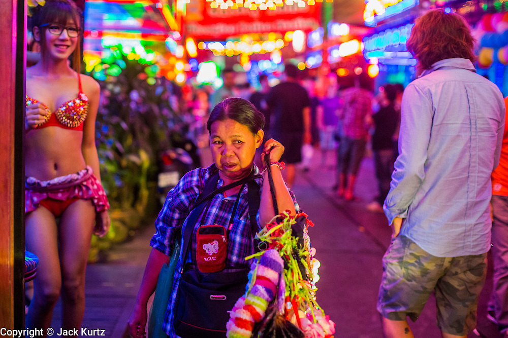 """12 JANUARY 2013 - BANGKOK, THAILAND:  A woman who sells garters to workers in the red light district of Soi Cowboy walks down the street between """"Ladyboy"""" entertainers and tourists. In Thai, the ladyboys are called kathoey. Many work in the entertainment and night life sectors of the Thai economy.  Prostitution in Thailand is illegal, although in practice it is tolerated and partly regulated. Prostitution is practiced openly throughout the country. The number of prostitutes is difficult to determine, estimates vary widely. Since the Vietnam War, Thailand has gained international notoriety among travelers from many countries as a sex tourism destination. One estimate published in 2003 placed the trade at US$ 4.3 billion per year or about three percent of the Thai economy. It has been suggested that at least 10% of tourist dollars may be spent on the sex trade. According to a 2001 report by the World Health Organisation: """"There are between 150,000 and 200,000 sex workers (in Thailand).""""    PHOTO BY JACK KURTZ"""