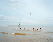 Bathing spectators enjoy fly-past by the 'Red Arrows', Britain's Royal Air Force aerobatic team in Clacton-on-Sea.