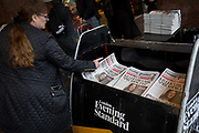 A commuter picks up a copy of the London Evening Standard newspapers with a headline about the latest on the rapid spread of the Chinese-source killer Coronavirus on their front pages, at Victoria station, on 30th January 2020, in London, England.