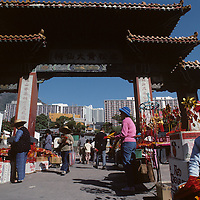 China, Hong Kong, Young boy sells souvenirs outside gates of Wong Tai Sin Temple in Kowloon Peninsula