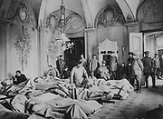 World War I 1914-1918:   French and German wounded soldiers lying on stretchers in a French chateau and being tended by medical staff.  Military, Army, Medicine