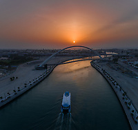 Aerial view of a boat under the Tolerance pedestrian Bridge in Dubai at sunset, U.A.E.