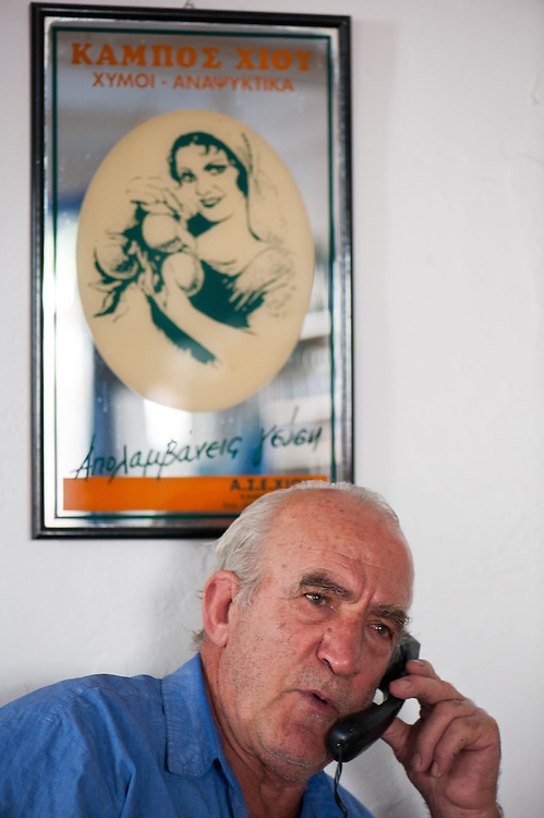 The owner of the coffee house of Pyrgi, Chios, chatting on the phone. Behind him an old advert for local Chios made fizzy drinks.