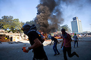 Protestors run past burning vehicles during clashes at Taksim Square Istanbul, Turkey on 11 June 2013. Turkish Prime Minister Recep Tayyip Erdogan  defended the police's latest show of force against demonstrators, as numerous arrests and injuries were reported in Turkey on 11 June after police and anti-government protesters clashed anew across Istanbul and authorities deployed tear gas, water cannon and armoured vehicles to clear demonstrators. In Istanbul's Taksim Square, which has become the centre of the anti-government protests, police moved in from the city's Besiktas district in the early morning, when only a few thousand demonstrators remained on the square after more than a week of occupation. Anti-government protests started there as a demonstration against a building project in the square's Gezi Park but have since grown into widespread condemnation of the government's conservative policies.