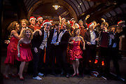 The cast of The Commitments perform a Christmas song outside the Palace Theatre in London's West End. As part of a PR launch for the production's Christmas season, the show's company stand outside the venue in the cold to sing one of their songs for passers-by and a video camera, used to promote the musical and attract more audiences. The girls wear low-cut red dresses and the boys santa hats. Roddy Doyle's best selling novel, The Commitments has been adapted into a full scale stage musical, and had its world premiere at the Palace Theatre in the Autumn of 2013.
