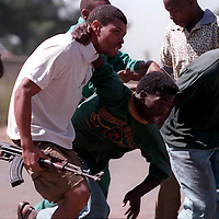 970104JS07:SAFRICA:UNREST:LIFE STYLES:APR94 -Self Defence Unit members carry an injured comrade hit by an Inkatha Fredom Party hostel gunfire, during an attack on the hostel by ANC self defence unit members.(Photo by Joao Silva/PictureNET)violence head shot hat AK