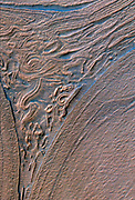 This image is from the floor of the Hellas Basin, a 1,400-mile wide impact crater. The landforms look almost as if they flowed like a viscous material. This image was taken by the High Resolution Imaging Science Experiment (HI RISE) camera on NASA's Mars Reconnaissance Orbiter on Dec. 26, 2009.