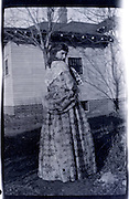 fashionable dressed young adult woman standing by house rural USA 1920s 1930s