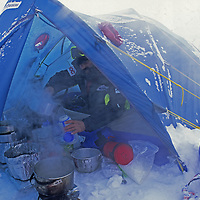 Guide Vern Tejas melts water during a storm on mountaineering expedition to lead 88-year old Norman Vaughan up a mountain named for him in Antarctica.