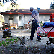 Joe Legree, of Beaufort, walks back towards his home with his two cats after loading his truck with a lawn mower before heading to work on Hilton Head Island on March 10, 2014.  Photograph was made off of Broad River Blvd. near Glaze Drive.