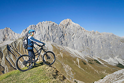 Mountain biker enjoying panoramic view on top of mountain, Tyrol, Austria