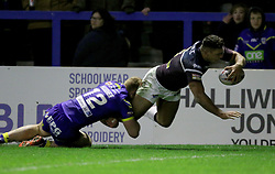 Leeds Rhino's Ryan Hall dives over to score as Warrington's Jack Hughes tackles during the Betfred Super League match at the Halliwell Jones Stadium, Warrington.