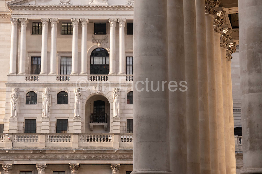 Mythical Greek male telamon figures look towards a female caryatid sculpture on the exterior of the Bank of England left and the columns of Royal Exchange right in the City of London, on 1st March 2021, in London, England.