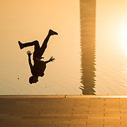 WASHINGTON, DC--A man does backflips next to the Reflecting Pool at sunrise.