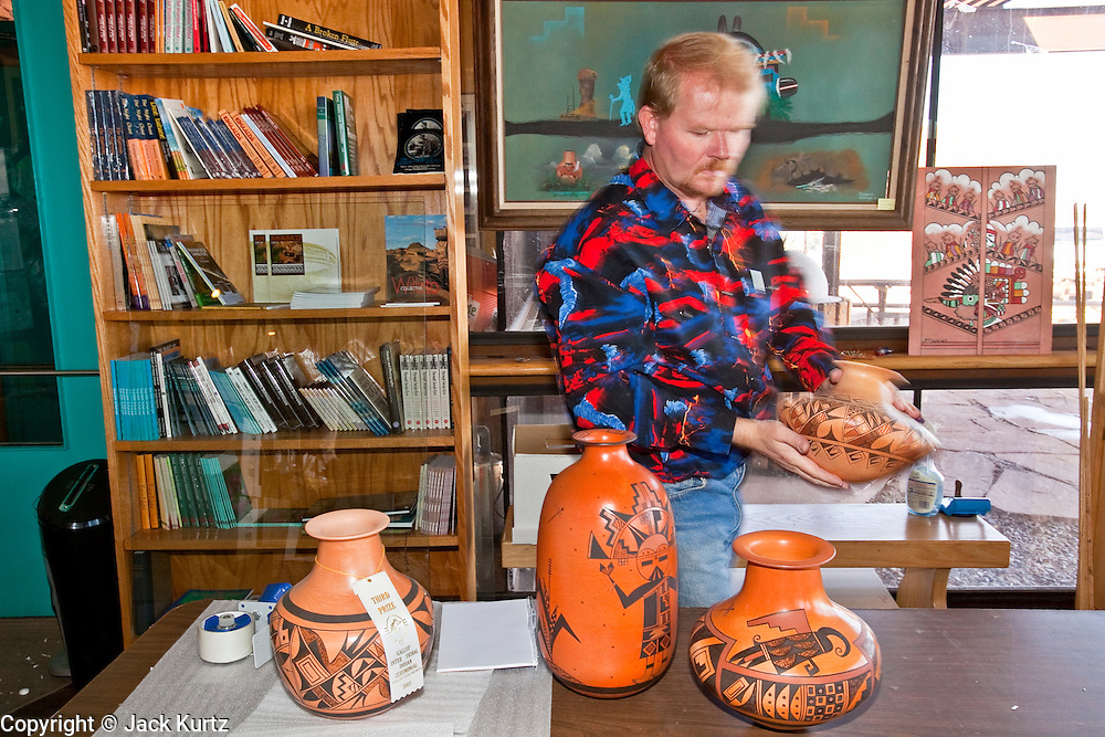 25 FEBRUARY 2010 -- WINSLOW, AZ: Kenn Evans II (CQ KENN WITH 2 n), a Park Ranger II, packs Hopi pottery for sale in the visitor center at Homolovi Ruins State Park north of Winslow. The park closed on Feb 22. The park's employees will spend the next few days packing up the park's exhibits but worry that the park's vulnerable archeological sites will be plundered by vandals and relic hunters when the park is vacant.   PHOTO BY JACK KURTZ