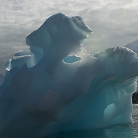 A weathered iceberg drifts in the Neumayer Channel near the Antarctic Peninsula, Antarctica. The foreground rocks are Damoy Point on Wiencke Island and the mountains are on Anvers Island.