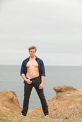 sexy man in an open shirt standing on a cliff by the sea