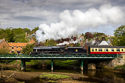 """© Licensed to London News Pictures. 18/05/2021. Ruswarp UK. 1945 LMS Stanier Class Locomotive 44871 """"Black Five"""" crosses the River Esk on route from Whitby to Pickering on the North Yorkshire Moors Railway this morning. The NYMR has started running its trains again this week as Lockdown measures are lifted. Photo credit: Andrew McCaren/LNP"""